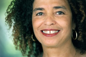 "Close-up portrait of Angela Davis in 1998, smiling, wearing dreads and hoop earrings. ""former commie Examiner/ Chris Hardy September 14, 1998"""