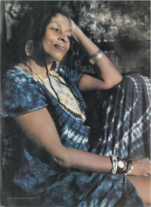 Photo of Assata Shakur in Cuba, wearing blue African dress and bangles, leaning her head on her left arm with a pensive half-smile.