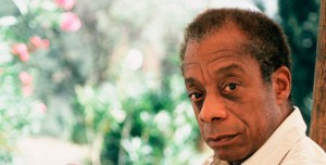 Photo portrait of older James Baldwin, 3/4 view of his head, facing left