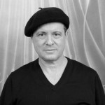 Publicity photo of Gil Fagiani in black sweater and beret looking straight at viewer.