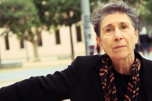 Photo portrait of Silvia Federici with gray hair looking intensely straight at the viewer
