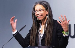 Half length photo of Ruth Gilmore at microphone wearing wire-rim glasses and long dreads, smiling with hands wide apart
