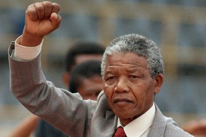 Mandela with raised fist, wearing suit and tie, at rally