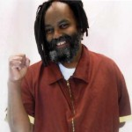Photo of Mumia Abu Jamal February 2012 soon after he was released from death row. Fist raised, smiling, wearing dreads and full beard.