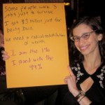 Photo of Karen Pittelman in glasses, smiling, holding placard opposing wealth inequality