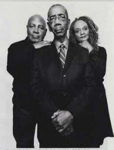 Black and white photo of Bobby Lee Rush in suit and tie with gray mustache, with Emory Douglas and Kathleen Cleaver behind him on either side, leaning on his shoulders