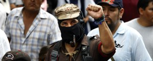 Photo of Subcomandante_Marcos with raised fist wearing black bandana over his face and a camouflage military cap