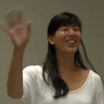 Ai-jen Poo in long black hair and white shirt waving to audience