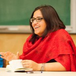 Photo of Harsha Walia sitting at desk wearing glasses, long dark hair, and a bright red wrap.