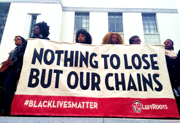 "Demonstrators holding banner reading ""NOTHING TO LOSE BUT OUR CHAINS"""