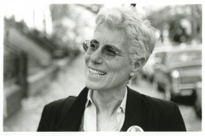 Black and White photo of Laura Whitehorn in glasses and gray hair, smiling