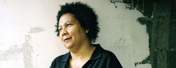 bell hooks with medium Afro, head cocked, against a concrete wall