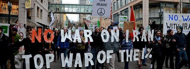 Protest march. Sign reads: No War on Iran - Stop Ware of the 1%