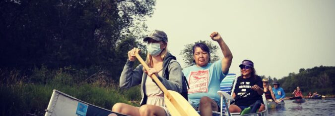 3 women water protectors in canoe. One in front with oar and mask. Two indigenous water protectors in back, one with fist raised.