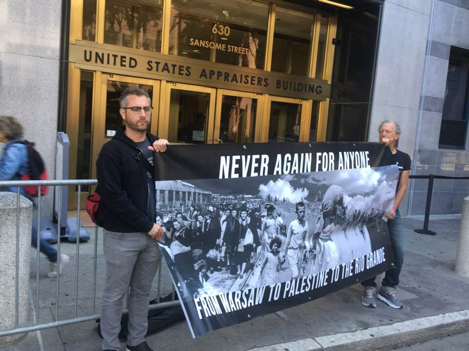 Two people stand with banner in front of ICE building. Sign reads Never Again for Anyone from Warsaw to Palestine to the Rio Grande