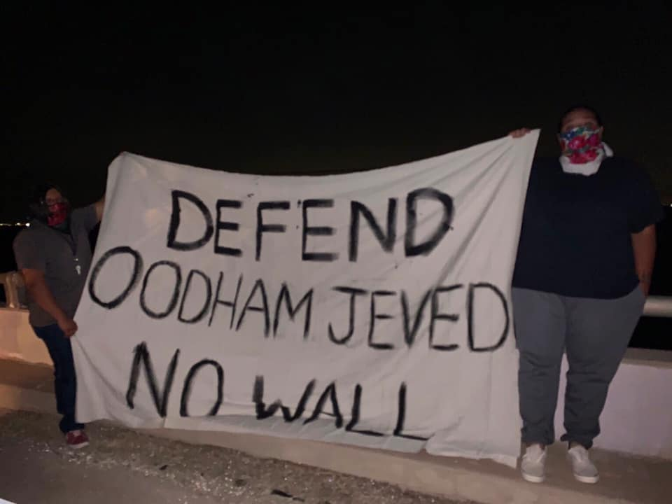 "Two protesters with masks hold a sign in the dark. Sign reads: ""Defend Oodham Jeved - No Wall"""